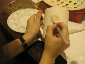 An attendee painting on ceramics