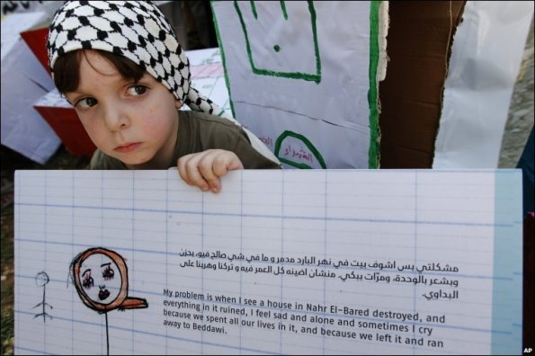 Photo from BBC News: A Palestinian boy holds a placard in Beirut, Lebanon